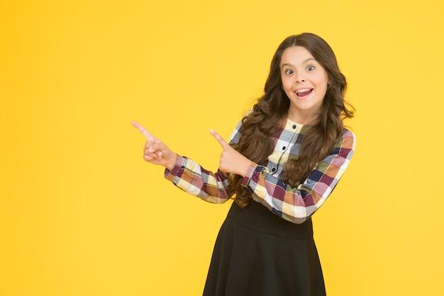 Controlla. ragazza felice che indica allo spazio giallo della copia del fondo. ragazzino con gesto di puntamento. dito indice che indica. indicando per la pubblicità. informazioni per la promozione. comunicazione visiva.