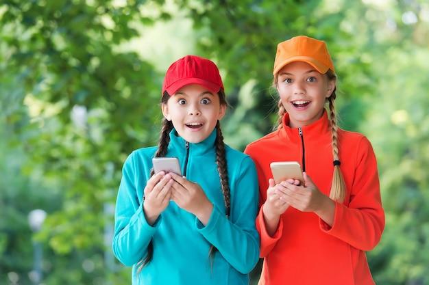 Controlla. bambini con smartphone. ragazze allegre migliori amiche. indossare abiti sportivi. ragazze adolescenti trascorrono del tempo insieme divertendosi. stile di vita digitale dell'infanzia. solidarieta. felice giorno dei bambini.