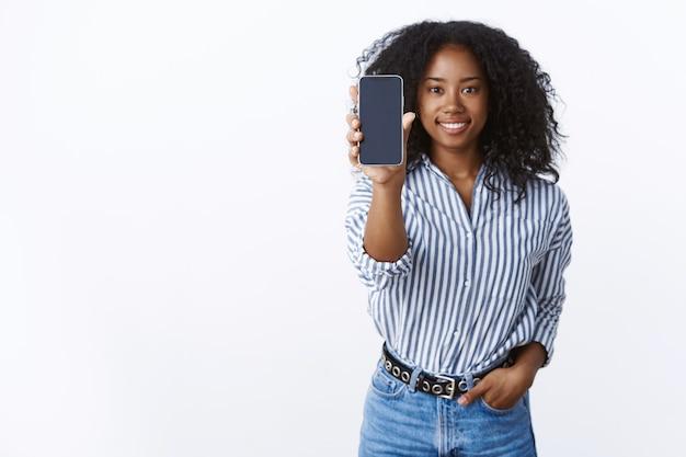 Controlla. ritratto piacevole spensierato affascinante donna dalla pelle scura sorridente felice acconciatura afro allungare il braccio che mostra il display dello smartphone sorridendo in attesa della tua opinione, presentando l'app