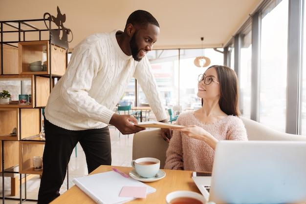 Controllalo per favore. il ragazzo attraente giovanile sta dando i suoi appunti alla sua studentessa internazionale mentre era seduto al caffè.