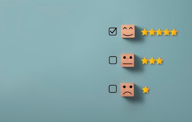 Segno di spunta per selezionare la faccia sorridente con cinque stelle su sfondo blu, concetto di valutazione del cliente.