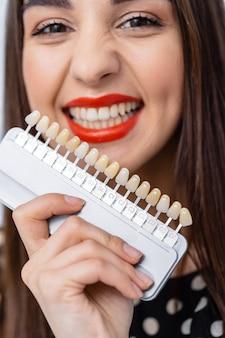 Controllare e selezionare il colore dei denti nello studio dentistico. processo di scelta del colore dei denti per una bella ragazza.