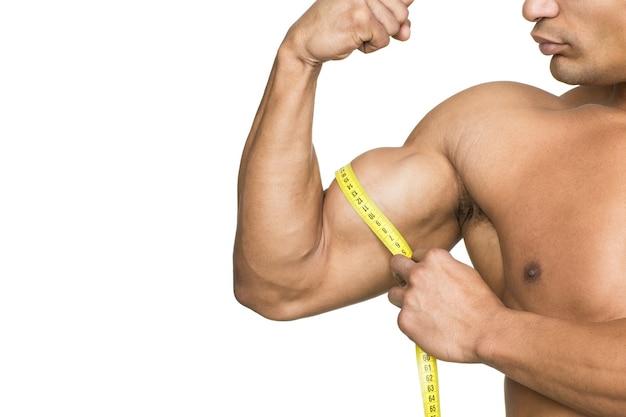 Controlla quei muscoli! ritagliata colpo di un bodybuilder strappato che misura i suoi bicipiti isolati su bianco