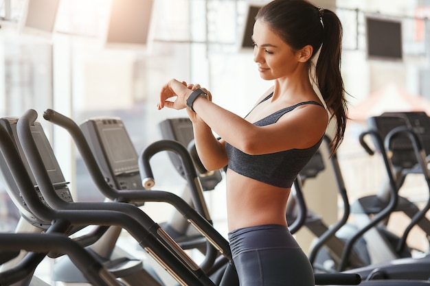 Controllo di tutti gli aggiornamenti bella e giovane donna che guarda il suo braccialetto sportivo mentre è in piedi