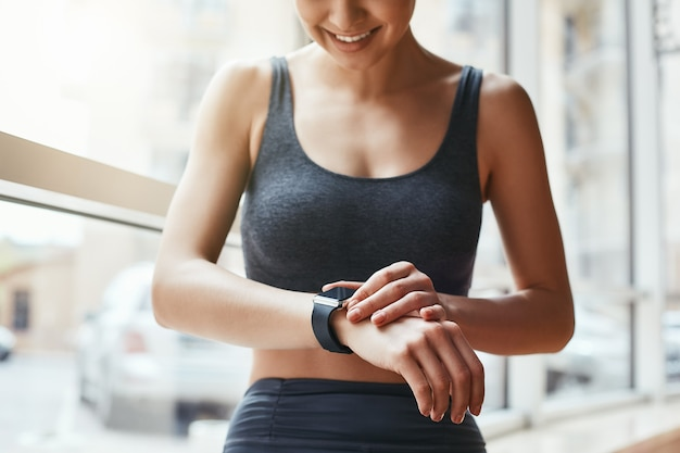 Il controllo di tutti gli aggiornamenti ha ritagliato la foto di una bellissima giovane donna che guarda il suo braccialetto sportivo mentre