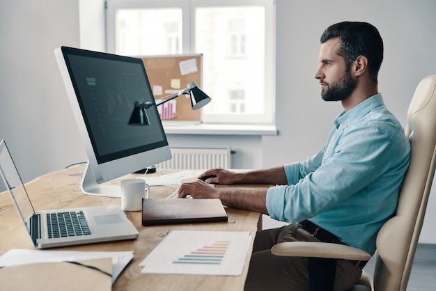 Verifica relazione annuale. giovane uomo d'affari moderno che analizza i dati utilizzando il computer mentre è seduto in ufficio