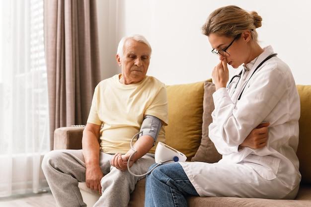 Controllo della pressione sanguigna. medico della giovane donna e uomo anziano.