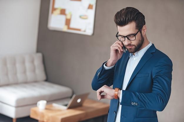 Controllo del suo orario. bel giovane con gli occhiali che parla al telefono cellulare e guarda il suo orologio da polso mentre è in piedi in ufficio