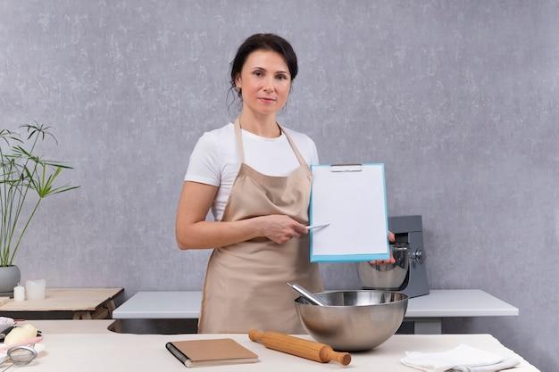 Verifica degli standard sanitari nelle cucine dei ristoranti. la donna in cucina tiene i documenti nelle sue mani.