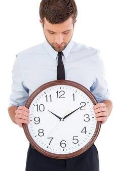 Controllo dell'ora. bel giovane in camicia e cravatta che tiene un orologio in mano e lo guarda mentre sta in piedi isolato su sfondo bianco