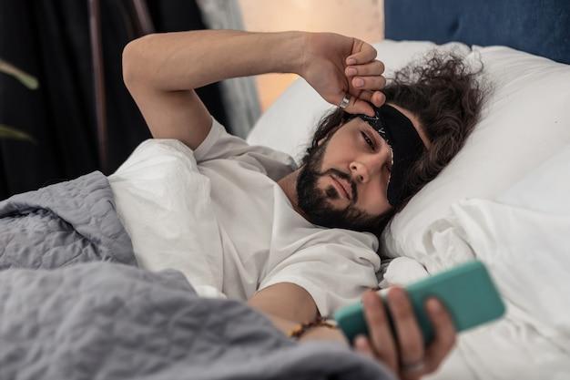 Controllo dell'ora. un bell'uomo assonnato che guarda il telefono mentre controlla l'ora al mattino