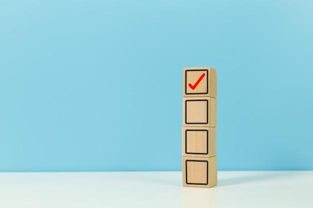 Lista di controllo e concetto di approvazione, blocco di legno con sfondo blu di icone di lista di controllo. risposta decisione sì voto.