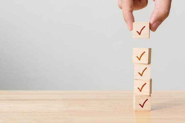 Concetto di lista di controllo, segno di spunta su blocchi di legno sul tavolo con spazio di copia