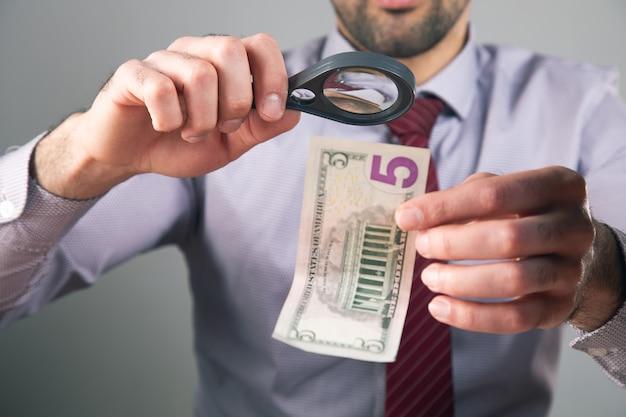 Controlla i soldi con una lente d'ingrandimento.
