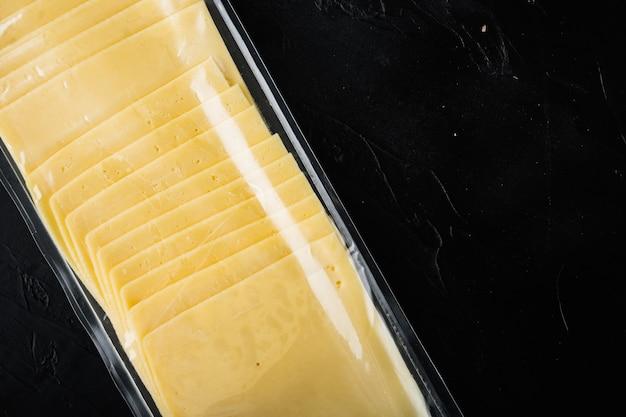 Formaggio cheddar in confezione sottovuoto, sulla tavola nera
