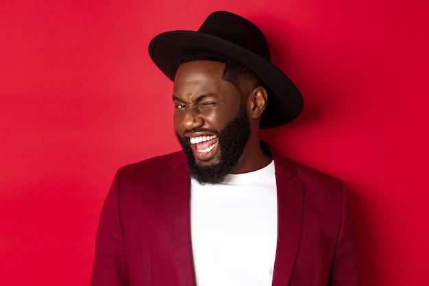 Uomo afroamericano sfacciato in abito da festa, strizzando l'occhio alla telecamera e sorridente, in piedi su sfondo rosso.