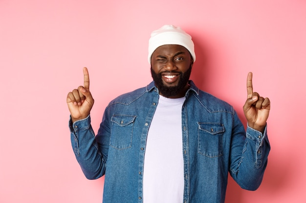 Uomo afroamericano sfacciato che sorride e fa l'occhiolino, mostrando un affare in cima, puntando le dita verso l'alto, in piedi su sfondo rosa