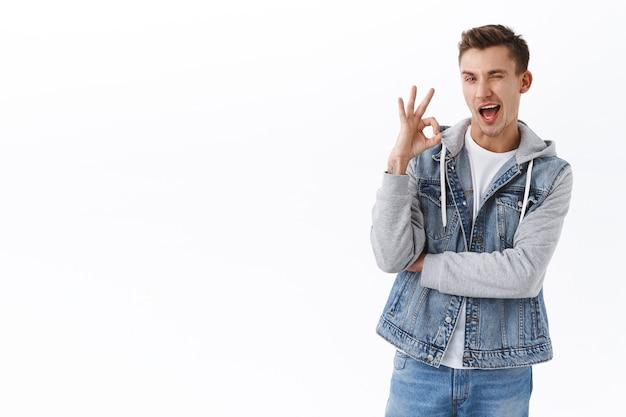 L'uomo gay sfacciato e civettuolo con i capelli biondi ha tutto sotto controllo, fa l'occhiolino civettuolo e sorride mostra il segno ok, non dire nessun problema, dare garanzia, consigliare il servizio aziendale o l'abbonamento
