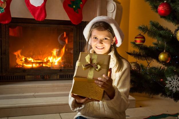 Allegra ragazza di 10 anni che guarda all'interno della magica scatola regalo di natale incandescente