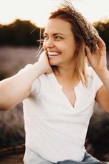 Donna caucasica adulta allegra che ride distoglie lo sguardo pur avendo una corona di fiori sulla sua testa in un campo di lavanda contro il tramonto.