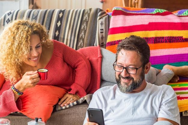 Una coppia adulta allegra si gode il tempo insieme a casa facendo colazione al mattino