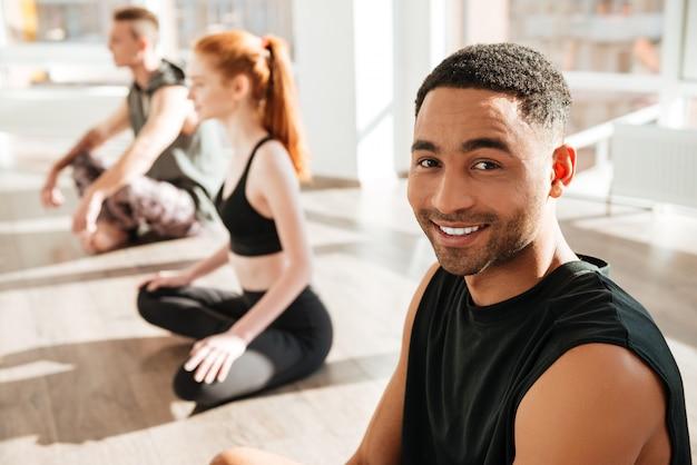 Yoga di pratica del giovane afroamericano allegro nel gruppo