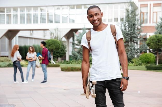Studente giovane afroamericano allegro con lo zaino in piedi e tenendo lo skateboard all'aperto
