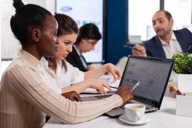 Allegra donna d'affari africana digitando sul computer portatile e sorridente seduto alla scrivania in un ufficio di avvio occupato. donna africana che utilizza laptop in sala riunioni, trattative parlando con i clienti