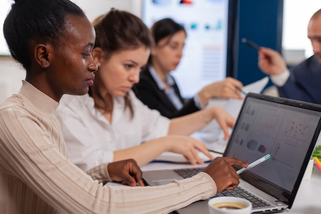 Allegra donna d'affari africana che digita sul computer portatile e sorride seduta alla scrivania in un ufficio di avvio occupato