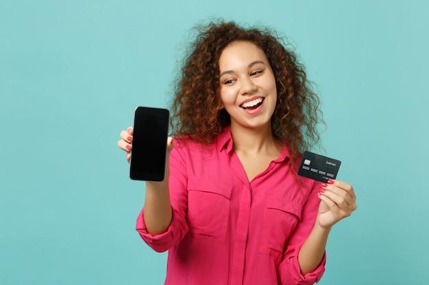 La ragazza africana allegra in abbigliamento casual tiene il telefono cellulare con la carta bancaria di credito dello schermo vuoto in bianco isolata su fondo blu del turchese. concetto di stile di vita di emozioni sincere della gente. mock up copia spazio.