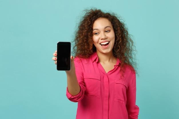 La ragazza africana allegra in abbigliamento casual tiene il telefono cellulare con lo schermo vuoto in bianco isolato sul fondo blu della parete del turchese in studio. persone sincere emozioni, concetto di stile di vita. mock up copia spazio.