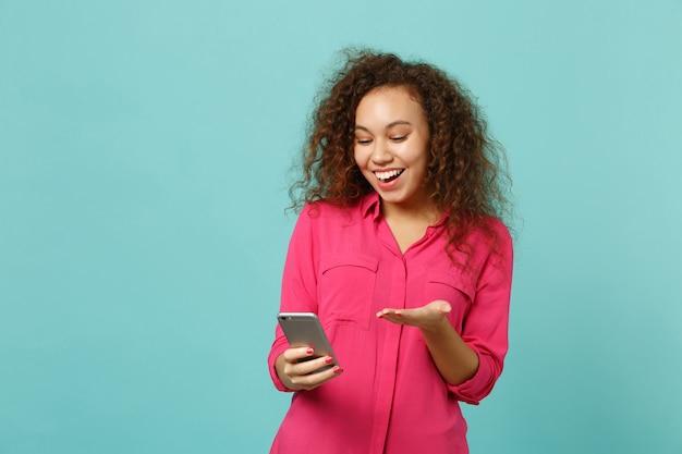 Ragazza africana allegra in abiti casual rosa utilizzando il telefono cellulare digitando messaggio sms isolato su sfondo blu muro turchese in studio. persone sincere emozioni, concetto di stile di vita. mock up copia spazio.
