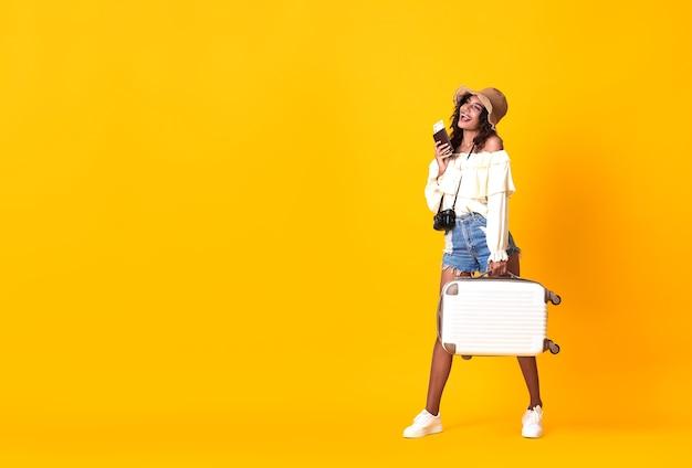 Allegra donna africana vestita in abiti estivi in possesso di passaporto con biglietto