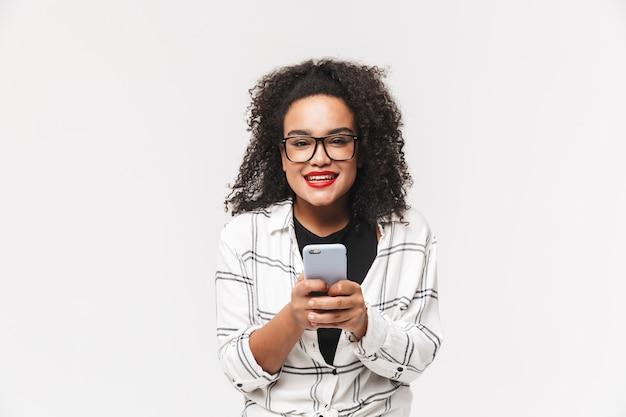 Allegra donna africana in occhiali tenendo lo smartphone e guardando direttamente su sfondo grigio