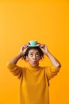 Donna africana allegra che indossa un maglione che tiene tazza con un piattino sulla sua testa isolata
