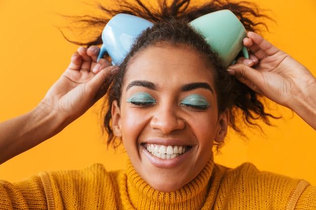 Allegra donna africana che indossa un maglione tenendo le tazze sulla sua testa isolata