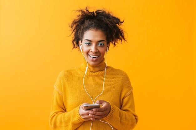 Allegra donna africana che indossa un maglione in piedi isolato, ascoltando musica con gli auricolari, tenendo il telefono cellulare