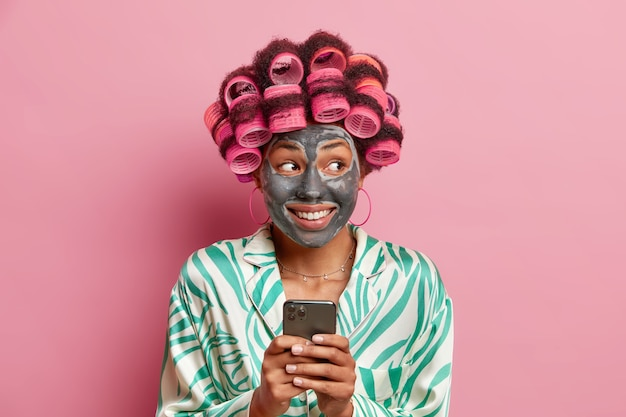 Allegra signora afroamericana sorride applicando positivamente la maschera di argilla usa il telefono cellulare per navigare in internet rende l'acconciatura perfetta vestita in abito domestico isolato su muro rosa