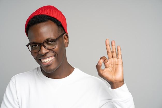 Allegro uomo afroamericano di buon umore che mostra il gesto giusto su grigio
