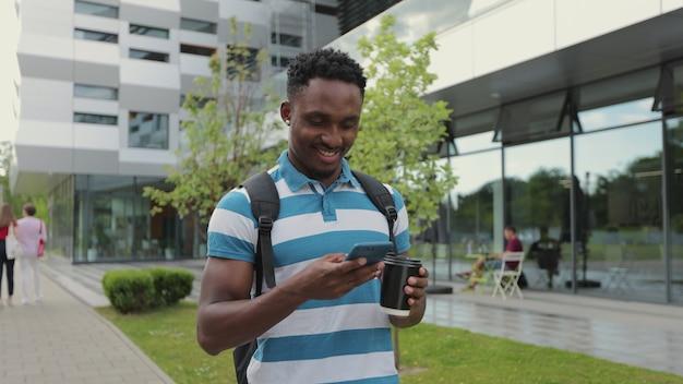 Ragazzo afro allegro che utilizza smartphone sullo sfondo dell'università bell'uomo afroamericano sorseggiando una bevanda calda per andare e parlare su smartphone mentre si cammina sui gradini sulla strada della città