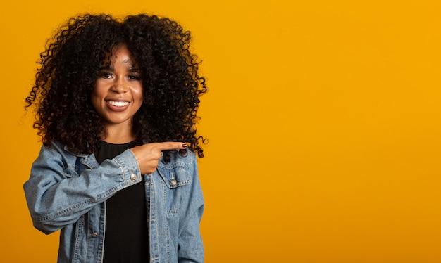 La donna allegra di afro indica via lo spazio della copia, discute il promo straordinario, lascia il posto o la direzione, indossa un maglione caldo giallo, ha un sorriso piacevole, si sente ottimista, isolata sopra la parete gialla.