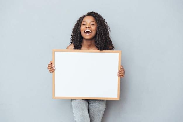 Donna afro allegra che mostra bordo bianco sopra il muro grigio