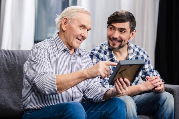 Allegro padre invecchiato e suo figlio seduti sul divano mentre si tiene una cornice per foto