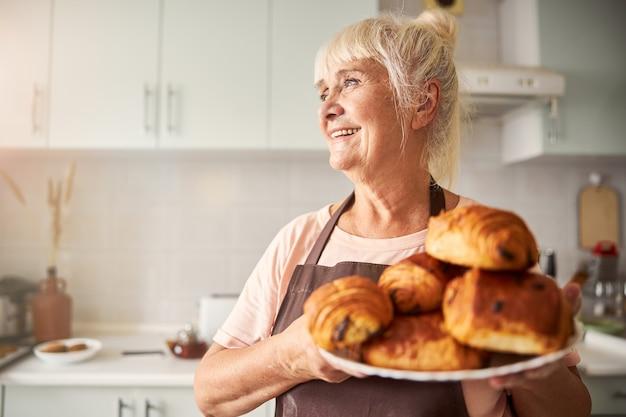 Signora anziana allegra in posa con piatto di prodotti da forno