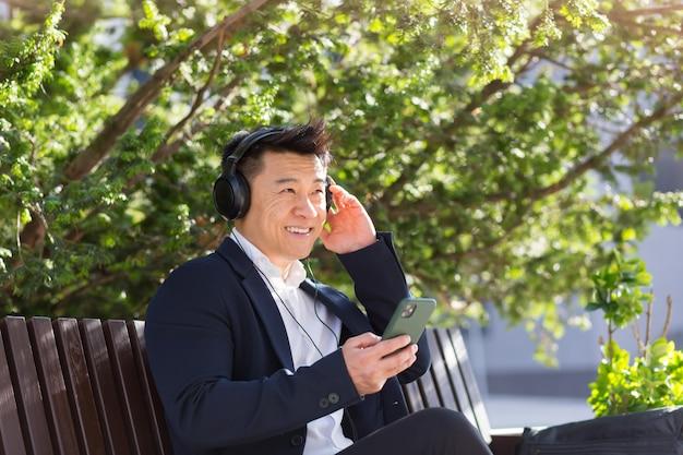Uomo d'affari asiatico allegro seduto su una panchina in un parco cittadino nel centro cittadino e ascoltando musica con le cuffie che tengono il telefono in mano. il maschio in giacca e cravatta gode della vita all'aria aperta. rilassati e riposati. stile di vita