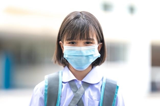 Bambini asiatici allegri studenti in uniforme da studente tornano a scuola con maschera medica dopo la pandemia di covid-19. torna al concetto di scuola stock photo
