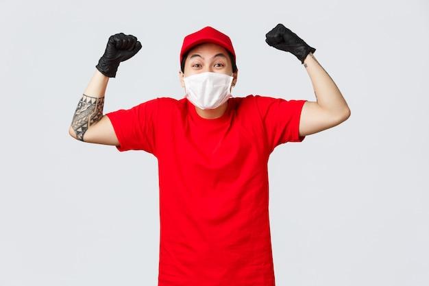 Allegro ragazzo delle consegne asiatico in maschera medica e guanti, indossando l'uniforme del corriere, cantando con la pompa del pugno, dicendo sì o evviva felice, festeggiando grandi notizie, ballo del campione, raggiungendo il successo