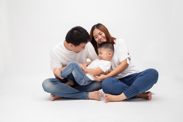 La famiglia asiatica allegra che si siede sopra la parete bianca si diverte il padre che solletica il piccolo figlio. giovani coppie con i bambini che indossano la cima e le blue jeans bianche. i genitori godono del tempo libero giocando al concetto