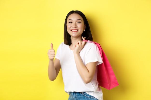 Cliente femminile asiatico allegro che sembra divertito, che tiene il sacchetto della spesa e che mostra i pollici in su