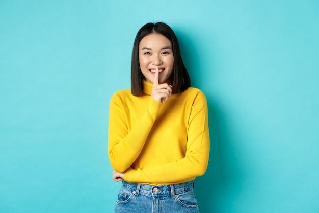 Allegra ragazza asiatica che chiede di essere in coda, zitto alla telecamera e sorridente, mantenendo il segreto, in piedi su sfondo blu.